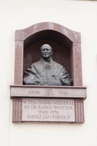 Tablica wmurowana w ścianę plebanii przy Kościele Św. Floriana w Krakowie.